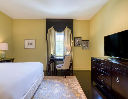 king room in hotel with bed, flat screen tv and desk area