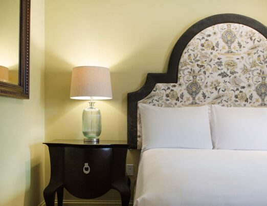 hotel suite with large king bed and close up shot of side table with lamp