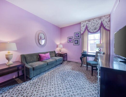 chic pink living space in hotel suite with couch, desk area and flat screen tv