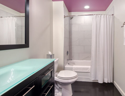 chic pink bathroom with sink counter, toilet and tub/shower