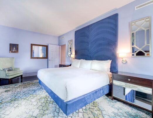 large king bed and tall headboard in hotel suite with accent chair in corner of room