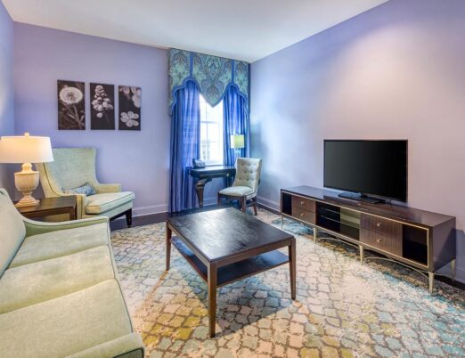 couch, armchair coffee table and flat screen tv in living space
