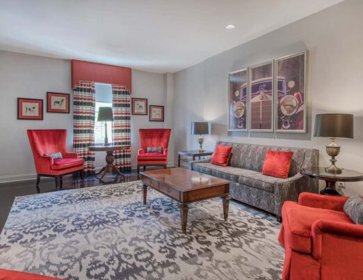 living space in hotel suite with couch, chaise, coffee table and large area rug
