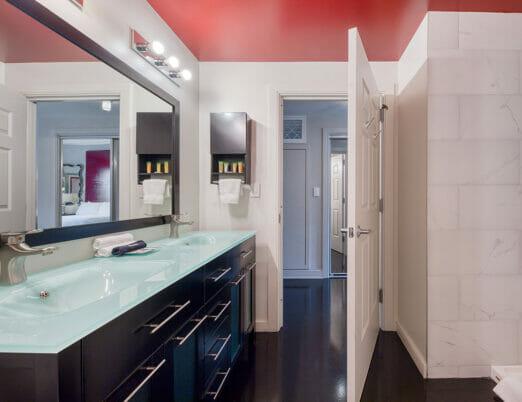 bathroom with door open showing double sinks and shower