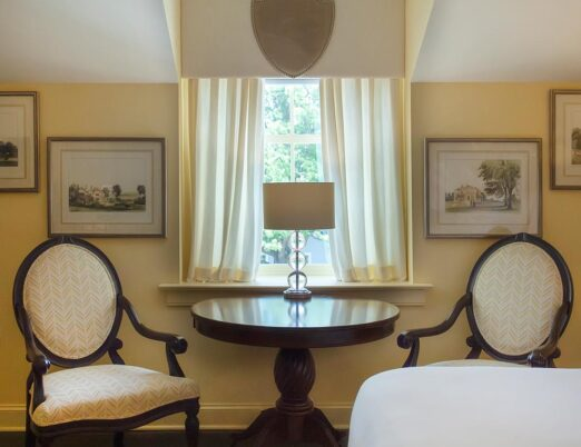 two arm chairs with table between holding lamp