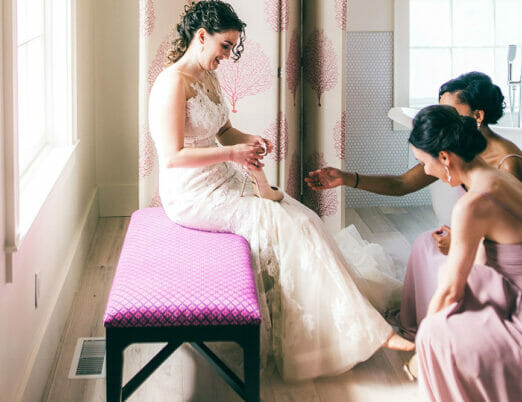 two bridesmaids helping put shoes on bride in hotel bathroom