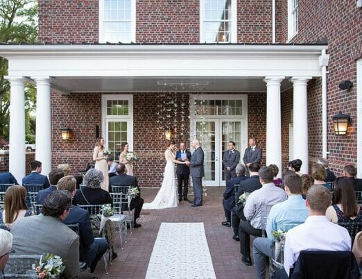 bride and groom being married infront of wedding ceremony on veranda