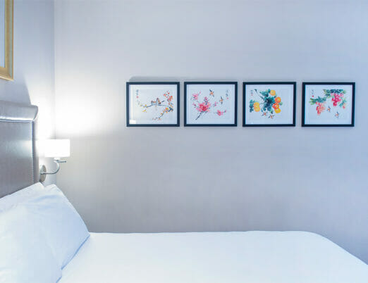 four framed images of artwork hung next to hotel bed
