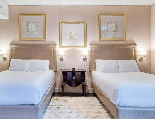 two beds in hotel room below hung artwork