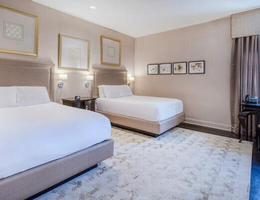 double queen hotel bedroom with artwork on walls