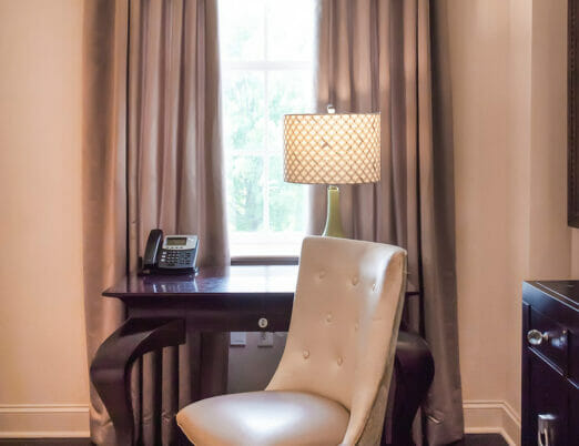 close up of desk area in hotel room with chair, table lamp and phone