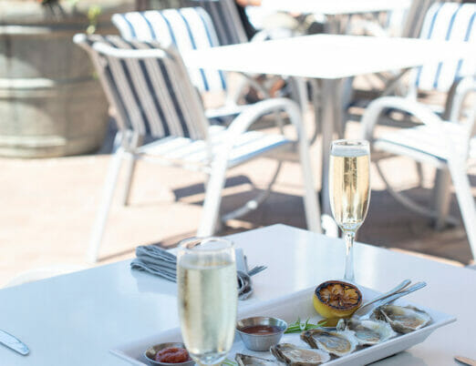 outdoor verandah dining table with two glasses of champagne and plate of six oysters