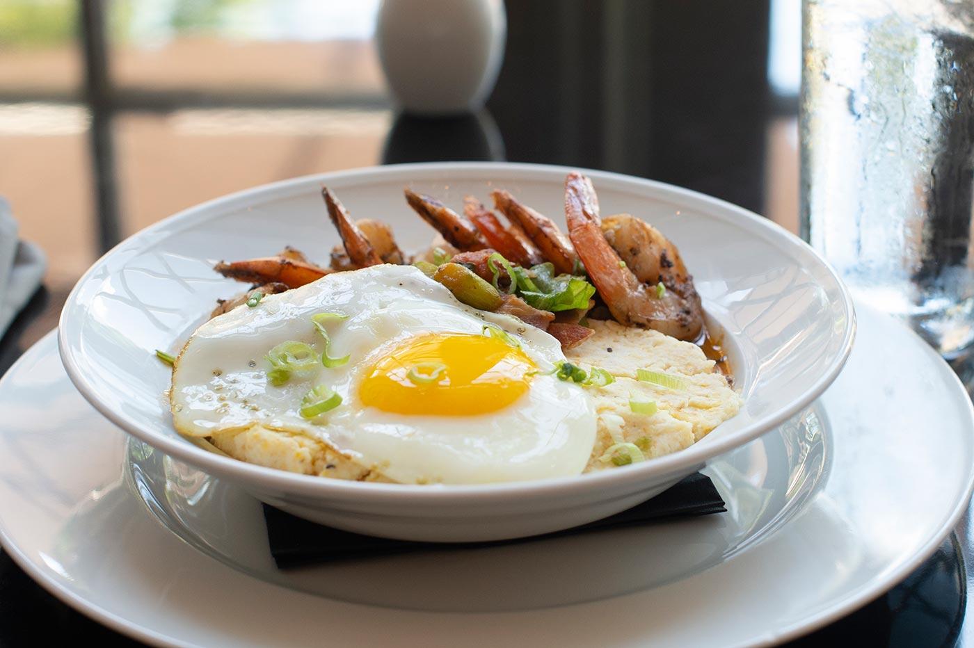 sunnyside up eye on scrambled eggs and side of shrimp