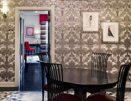 dining table with four chairs in wallpapered room next to bedroom