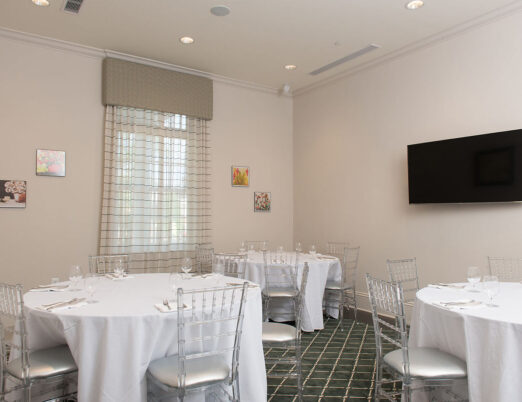 meeting space with window drapery, flat screen tv and three round tables for dining