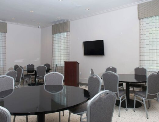 business meeting space with flat screen, podium and round dining tables