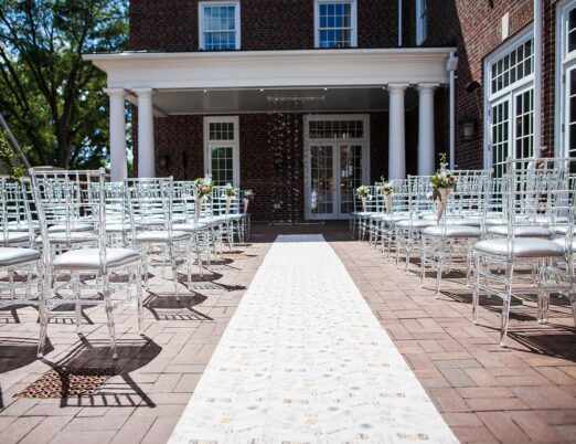 summertime wedding ceremony setup with rows of clear chairs, runner down the aisle on veranda