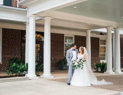 bride and groom smiling outside of exterior of The Mayton hotel