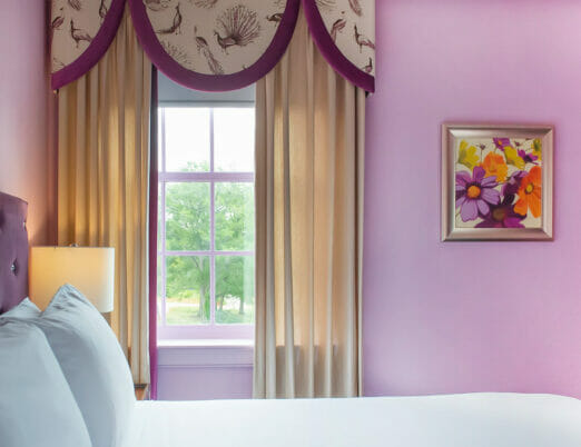 pink hotel bedroom with flower artwork hung on the wall next to window