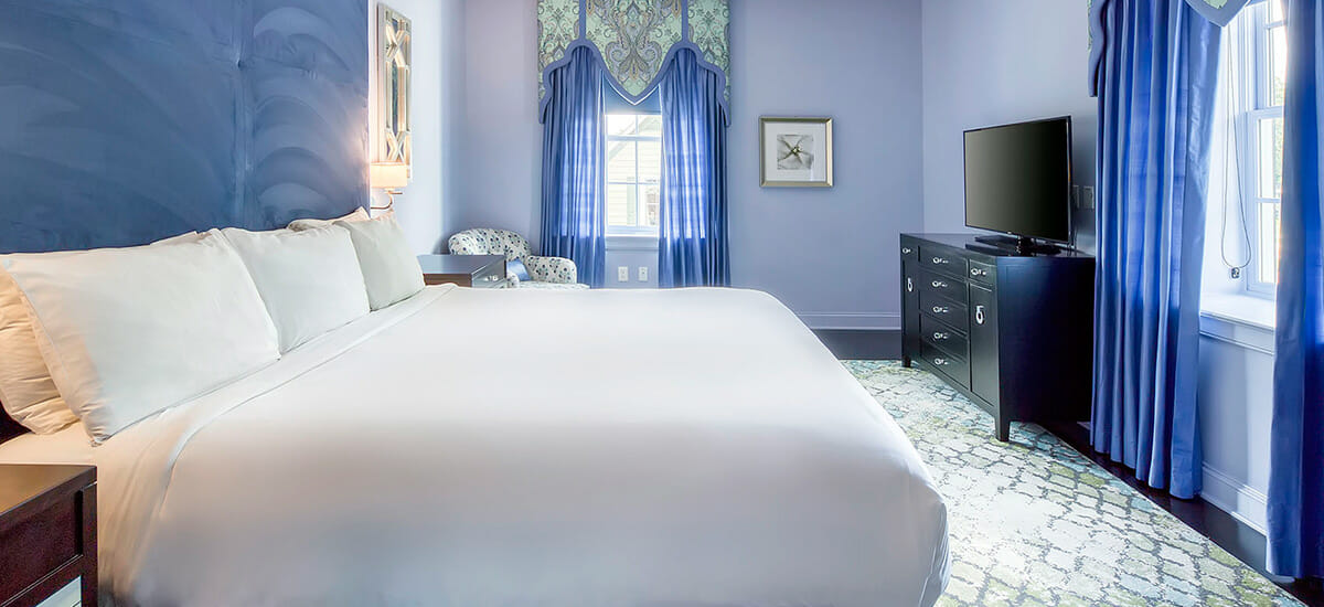 large king bed in hotel suite with tall headboard in blue room