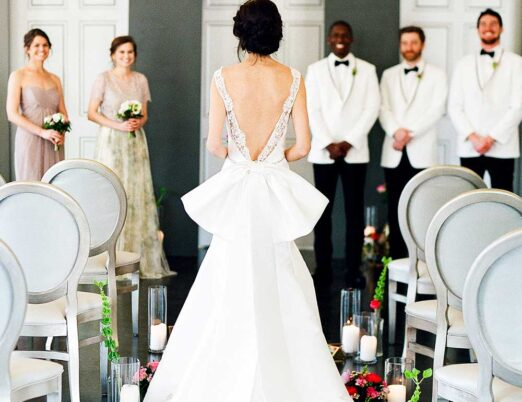 back of bride walking down aisle showing bow on back of dress