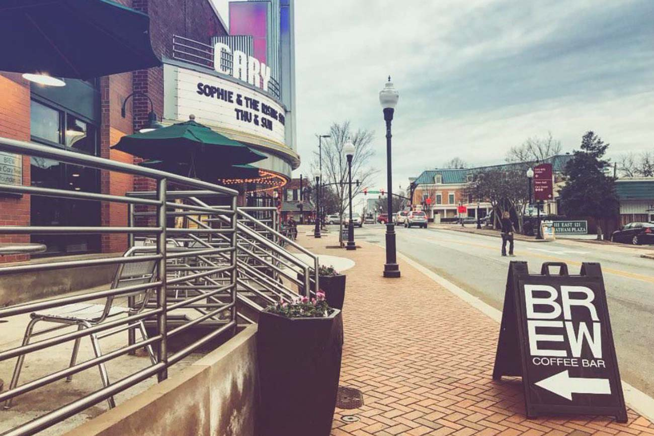 a quiet downtown street in Cary, NC with a sidewalk sign for BREW Coffee Bar and a heritage movie theater