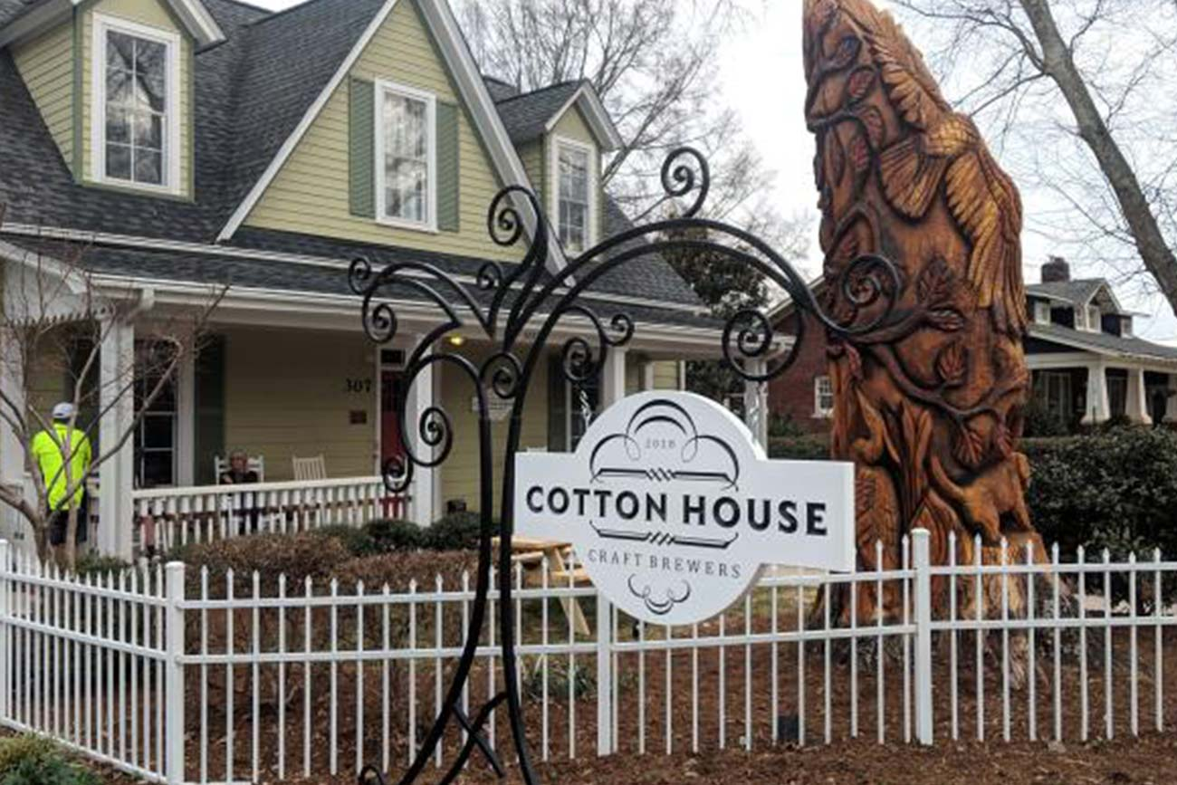 "a sign saying ""Cotton House Craft Brewers"" in front of a 2 story green house"