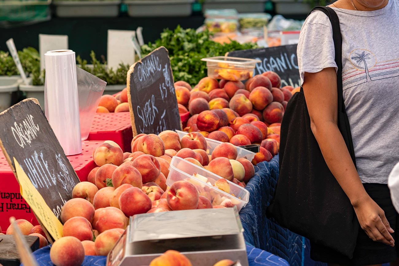 a farmer's market stand with piles of organic peaches