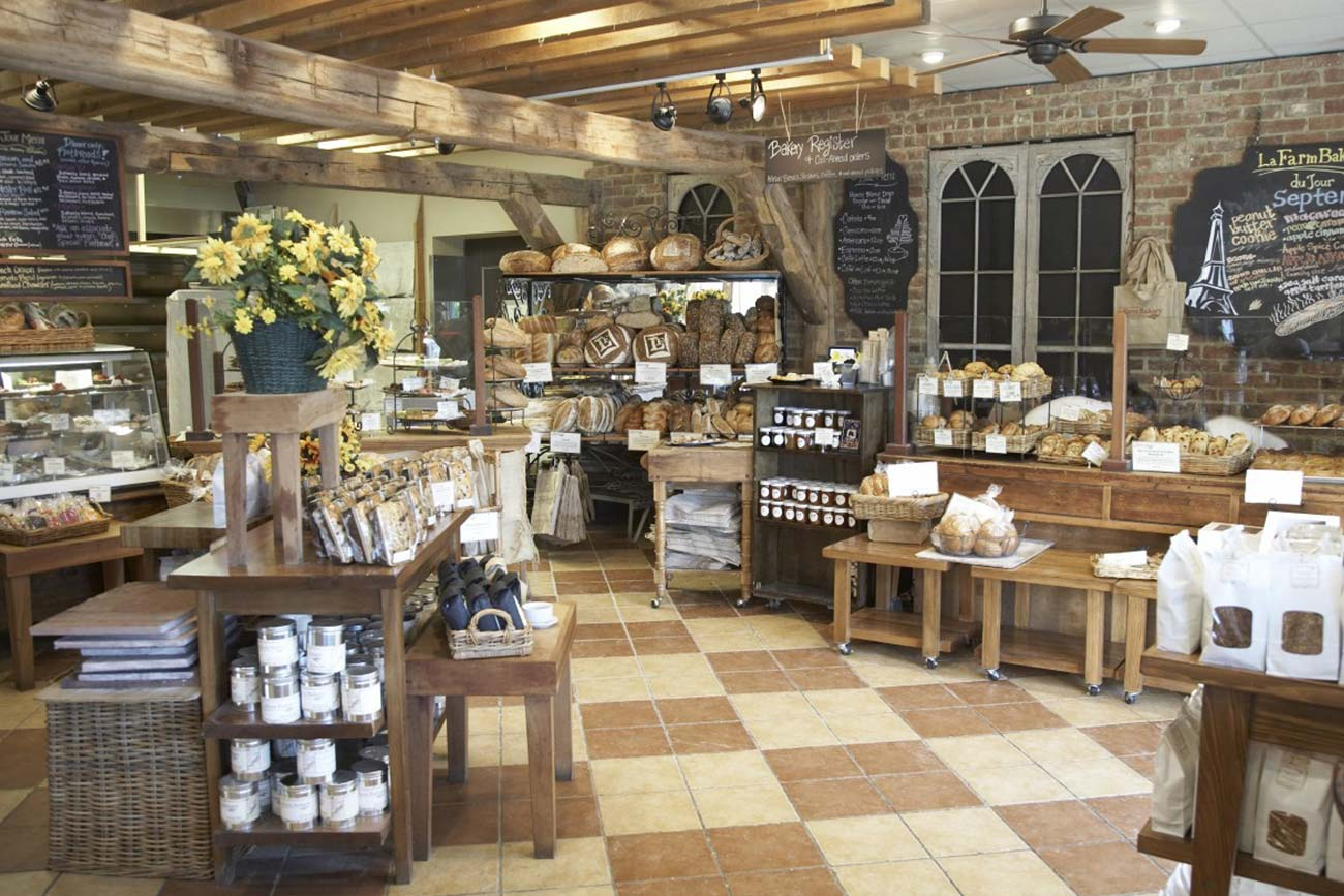 a heritage bakery with stone floors and brick walls and shelves full of rustic loaves of bread
