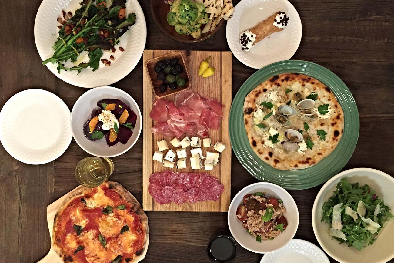 looking down at an array of plated restaurant dishes including pizzas, salads, meat and cheese board, and dessert pasteries