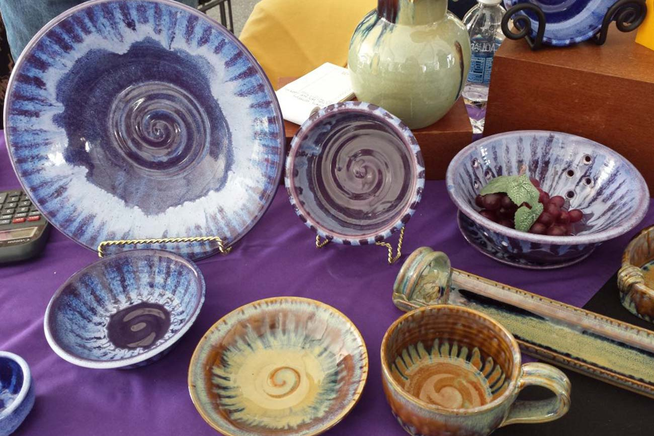 handmade pottery with swirling patterns in purple and brown on display at a pottery studio