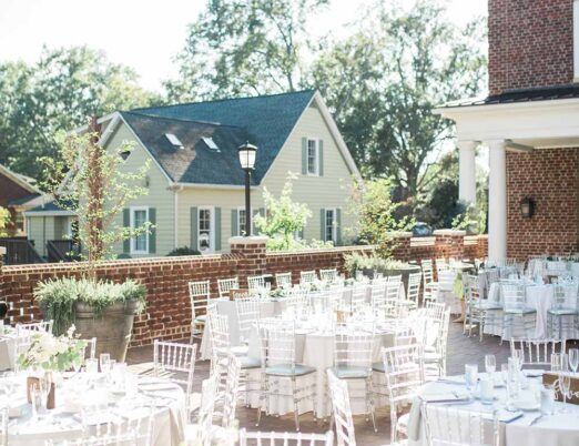 sunny outdoor event space on terrace with round dining tables for wedding or fancy event