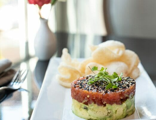 an appetizer of tuna tartare with avocado and crispy chips