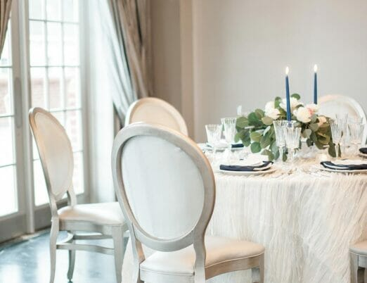 round table with long white linen, candle centrepiece, and placesettings