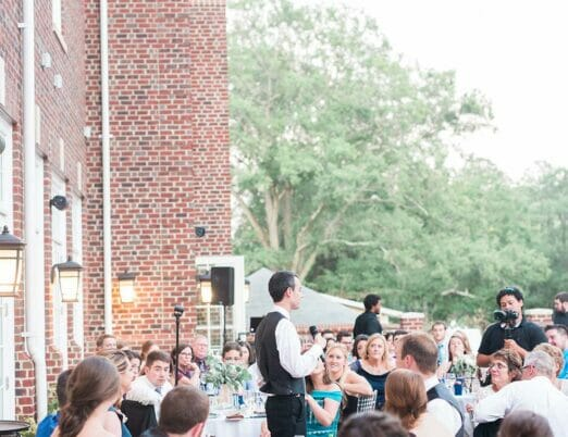 man giving speech at hotel wedding reception outdoors