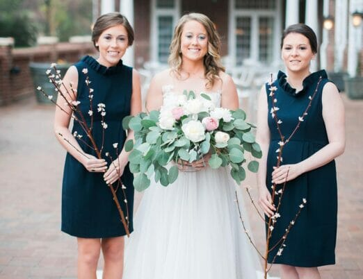 bride and two bridesmaids smiling on veranda holding flowers