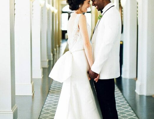 bride and groom in hotel hallway holding hands standing in front of one another smiling