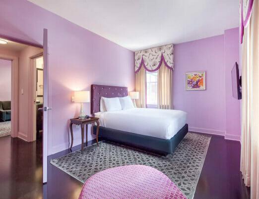 queen bedroom in pink hotel room