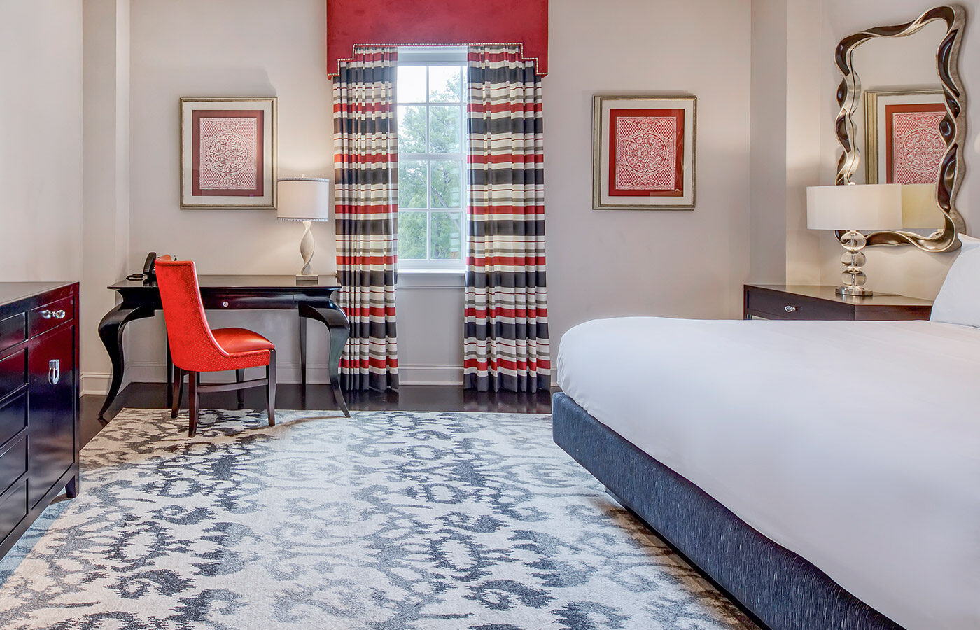large king bed in hotel suite with desk area in front of window