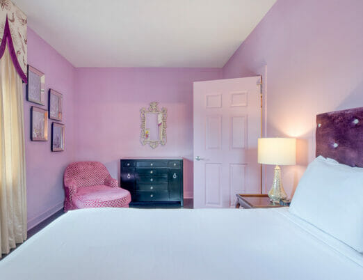 queen bedroom in pink hotel room with a chair and a dresser