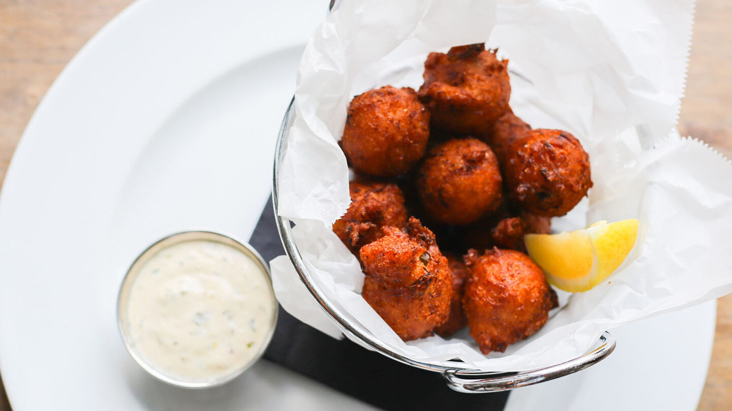 a hushpuppies appetizer of deep fried cornmeal and dipping sauce