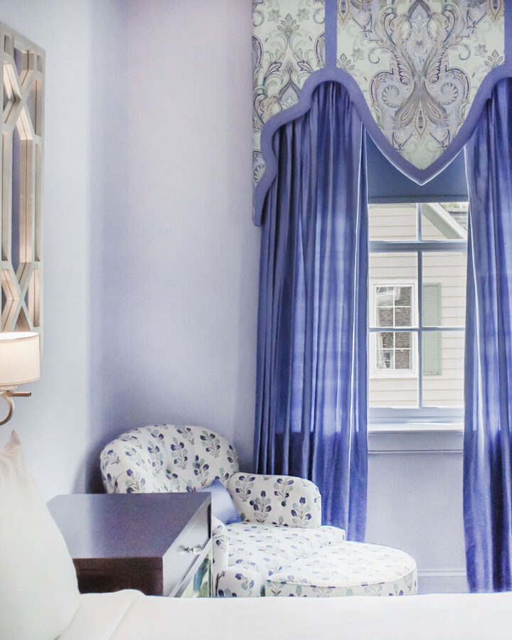 a bed, bedside table, and bedside chair in a luxury hotel room with light purple walls and purple drapes
