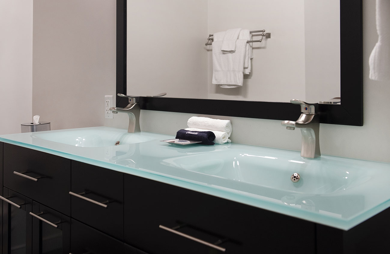 a double sink vanity and large mirror in a hotel room bathroom
