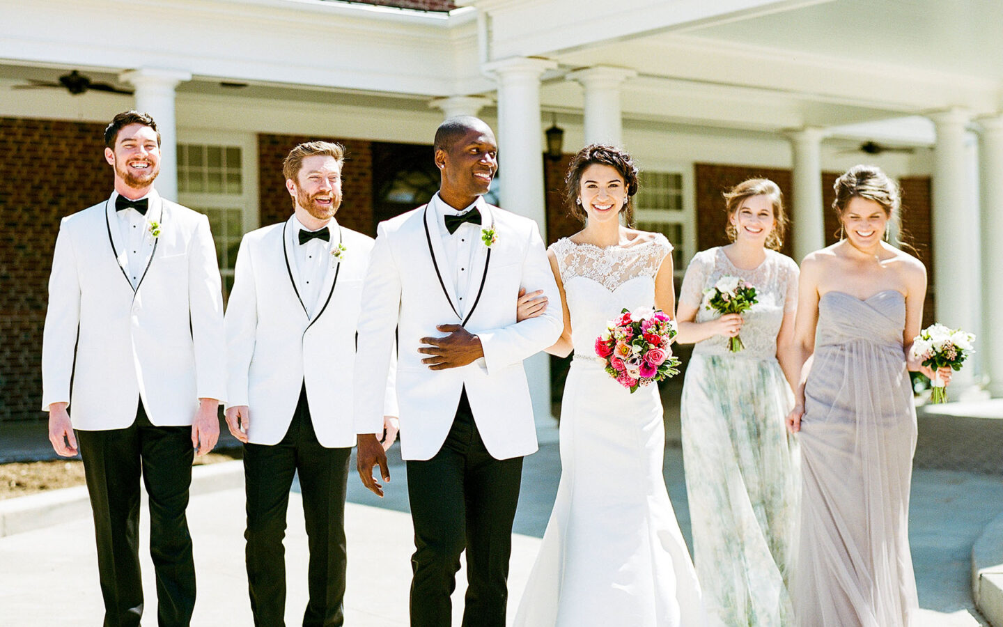 a bride and groom posing with members of their wedding party
