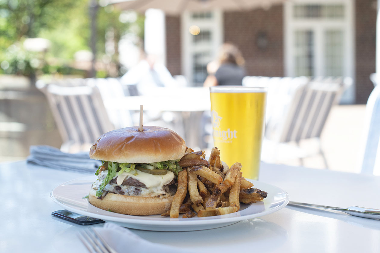 a plate of burger and fries beside a glass of beer on an outdoor terrace